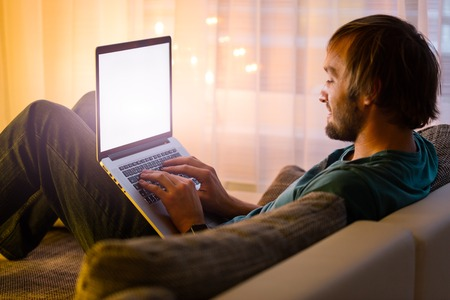 luxury apartment: Young man working on modern laptop in cozy home Stock Photo