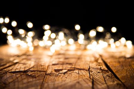 natale: Sfocatura luci di Natale su tavole di legno, bassa profondità di messa a fuoco con copyspace
