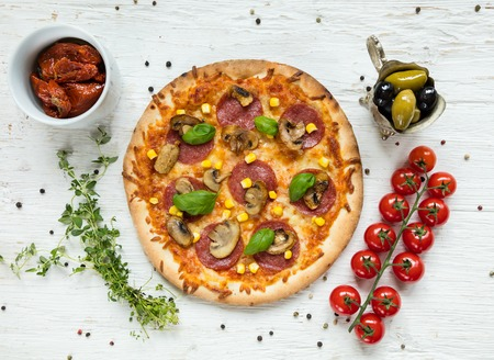 italy food: Delicious italian pizza served on wooden table, shot from above