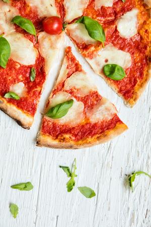 上から撮影、木製のテーブルで提供していますイタリアのおいしいピザ