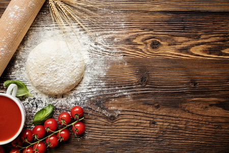 Pizza dough with ingredients on wood, shot from above Stockfoto