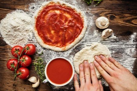 Verse originele Italiaanse rauwe pizza voorbereiding, close-up van de mens handen in actie Stockfoto