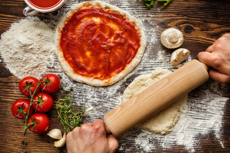 preparación fresca original de la pizza italiana cruda, primer plano de las manos del hombre en la acción Foto de archivo