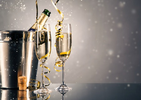 Pair glass of champagne with bottle in metal container. New Year celebration theme with blur spots of bubbles Stockfoto