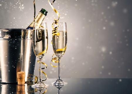 felicitaciones: vidrio par de champán con la botella en un contenedor de metal. Celebración del Año Nuevo tema con manchas de la falta de definición de las burbujas
