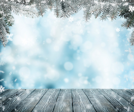 Abstract snowy background with frozen fir branches and empty wooden planks