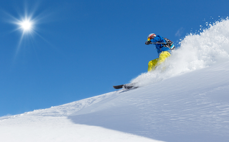 a slope: Man skier running downhill on sunny slope