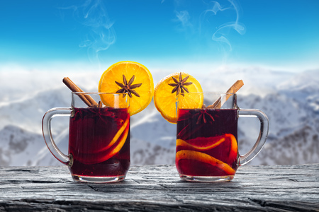 vin chaud: Hot red wine drinks on wooden table with blur winter landscape