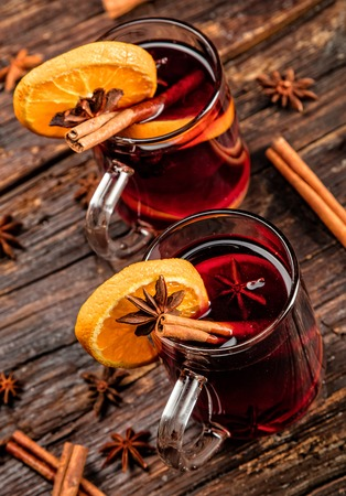 vin chaud: Hot wine drinks with spicy and sweet arrangement, Shot on old wooden table
