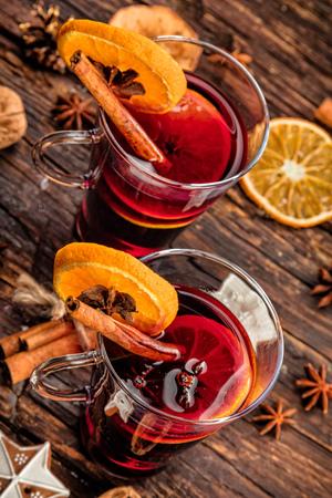 vin chaud: boissons vin chaud avec arrangement épicé et sucré, Prise de vue sur la vieille table en bois Banque d'images