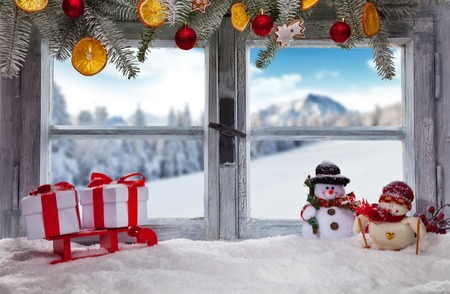 Atmospheric Christmas window sill decoration with snowy landscape outside Archivio Fotografico