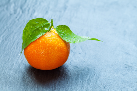 dewy: Fresh dewy mandarin placed on black stone. Copyspace for text