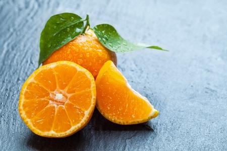 dewy: Fresh dewy mandarin placed on black stone. Stock Photo