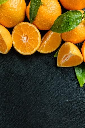 fruit orange: fruta fresca de naranja colocada en la piedra negro. Disparo de vista aérea