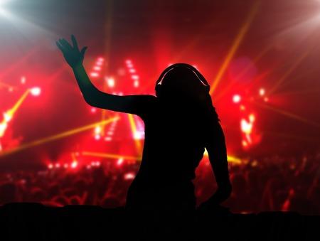 party dj: DJ con los auriculares en la noche del partido del club bajo las luces del punto y la gente se aglomera en el fondo