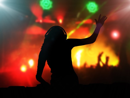 music background: DJ with headphones at night club party under the spot lights and people crowd in background Stock Photo