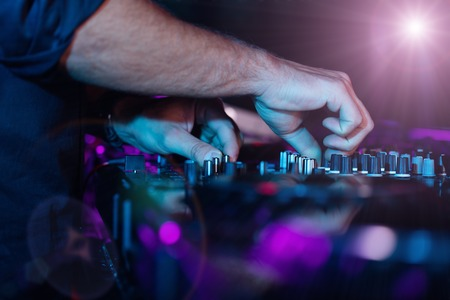 dj turntable: DJ turntable console mixer controlling with two man hands Stock Photo