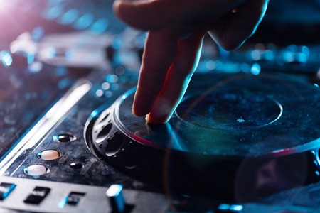 dj party: DJ turntable console mixer controlling with hand Stock Photo