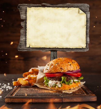 hamburger steak: Delicious home made hamburger with blank blackboard, served on wooden desk. Copyspace for text