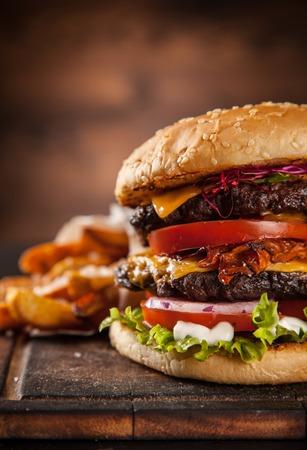 Heerlijke zelfgemaakte hamburger met sla en kaas, geserveerd op houten bureau