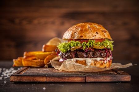 Leckere hausgemachte Hamburger mit Salat und Käse, serviert auf Holz-Schreibtisch Lizenzfreie Bilder
