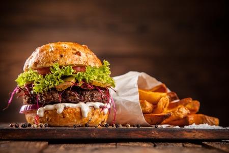Heerlijke zelfgemaakte hamburger met sla en kaas, geserveerd op houten bureau Stockfoto