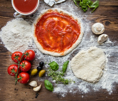 tomato sauce: Pizza dough with tomato sauce on rustic wooden table Stock Photo