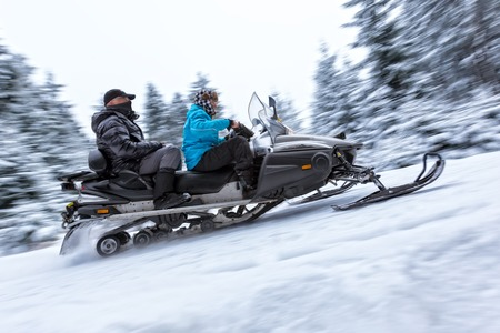snowmobile: Snowmobile on a winter forest road in blur motion movement