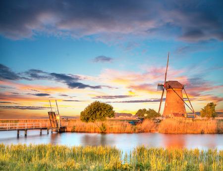 nederland: Windmills and water canal in Kinderdijk, Netherlands. Beautiful sunset sky