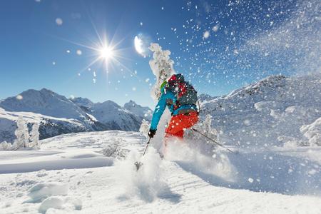 Man freeride skier running downhill on sunny Alps slope.