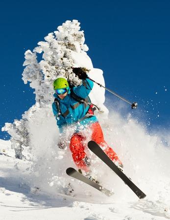 downhill: Man freeride skier running downhill and jumping