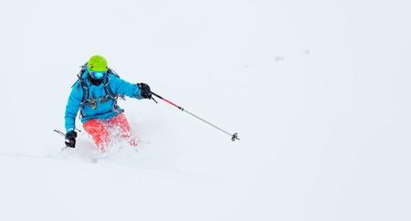 powder snow: Man freeride skier running downhill in powder snow. Copyspace for text
