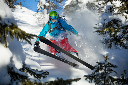 alpinist: Action photo of young man freeride skier running downhill in forest