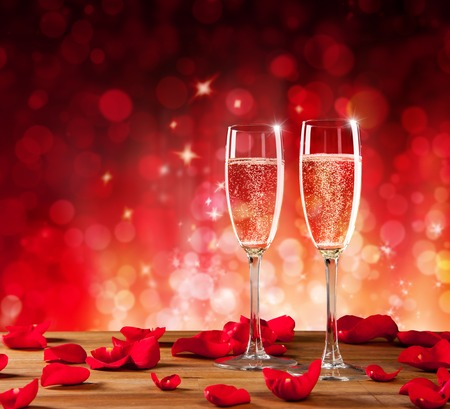 Het stilleven van valentijnskaarten met champagne en rode rozenbloemblaadjes met onduidelijk beeld abstracte achtergrond. Copyspace voor tekst