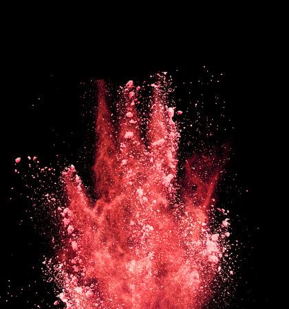 赤い粉、黒の背景で隔離の爆発 写真素材