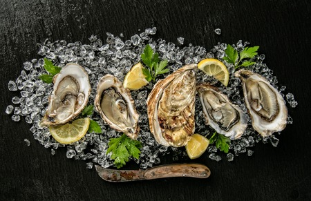 Oysters served on stone plate with ice drift, knife and lemon.