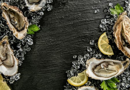 shellfish: Oysters served on stone plate with ice drift and lemon.