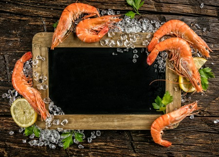 Prawns served on wood with empty blackboard, knife and lemon.