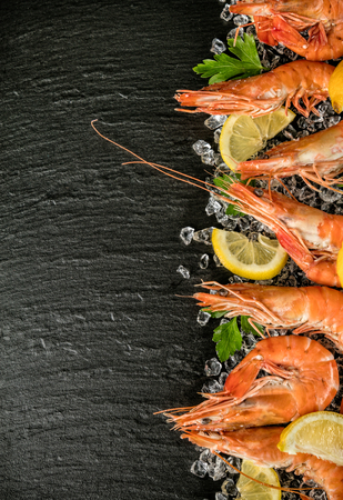 prawn: Cooked prawns served on black stone, placed on ice drift