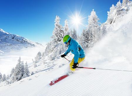 powder snow: Man skier running downhill on sunny Alps slope Stock Photo