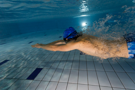 swim: Young man swimming in pool. Concept of healthy lifestyle. Underwater photography Stock Photo