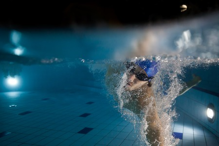 Young man swimming in pool. Concept of healthy lifestyle. Underwater photography Stock Photo