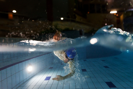 Young man swimming in pool. Concept of healthy lifestyle. Underwater photography