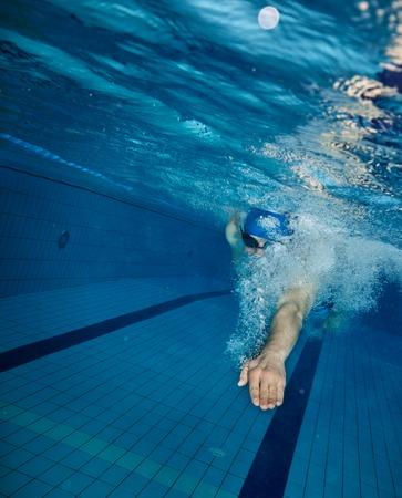 若者はプールで泳ぐ。健康的なライフ スタイルのコンセプトです。水中写真