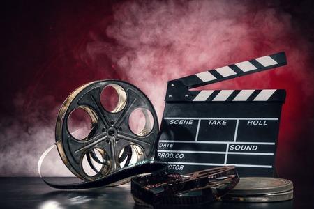 rollo pelicula: Retro accesorios de producción de películas de naturaleza muerta. Concepto de la cinematografía. efecto sobre el fondo del humo