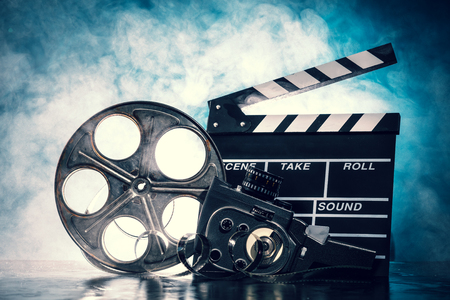 old movies: Retro film production accessories still life. Concept of filmmaking. Smoke effect on background