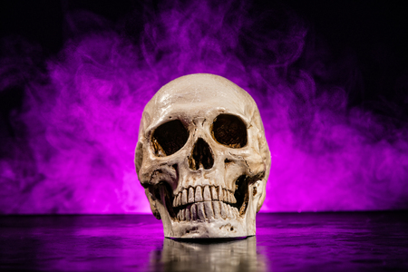 deadly poison: Old human skull head with smoke on dark background Stock Photo