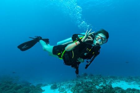 picada: Hembra joven buzo bajo el agua que muestra señal de ok Foto de archivo