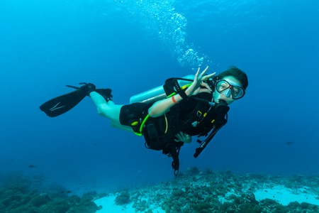 Young female scuba diver underwater showing ok signal