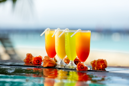 natural pool: Fresh summer cocktails drinks placed next to swimming pool with ocean on background.